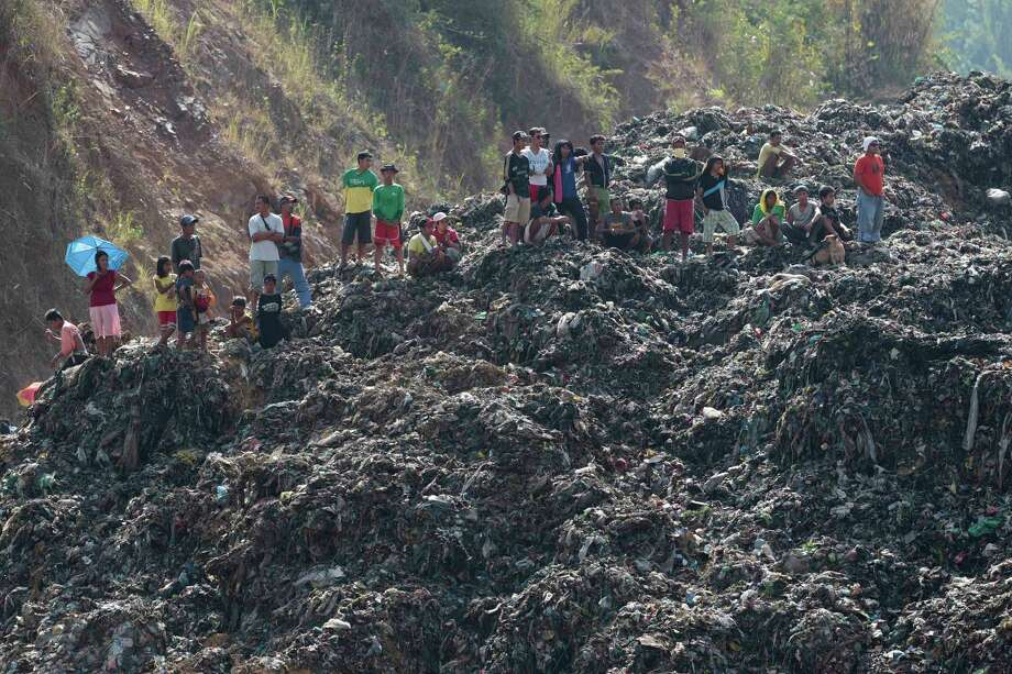 Workers and residents stand on a mountain of garbage at a landfill during a rescue operation in San Isidro, Rizal province, east of Manila, Philippines on Saturday April 20, 2013. Police said 4 workers were reportedly missing after after a garbage landfill slid along a mountainside April 19. Photo: AP