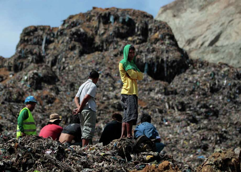 Workers and residents wait for news on a mountain of garbage at a landfill during a rescue operation in San Isidro, Rizal province, east of Manila, Philippines on Saturday April 20, 2013. Police said four workers were reportedly missing after the garbage landfill slid along a mountainside on Friday. Photo: AP