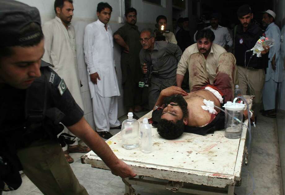 An injured police officer is rushed to an emergency ward following a suicide attack in Peshawar, Pakistan on Tuesday, April 16, 2013. A suicide bomber targeting members of an anti-Taliban political party in northwestern Pakistan killed many people and wounded others, police and hospital officials said. Photo: AP