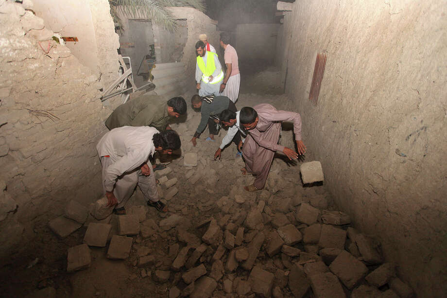 In this photo taken Tuesday, April 16, 2013, Iranians clear a route at the Gosht district after an earthquake hit southeastern Iran. The earthquake toppled homes and shops on both sides of the Iran-Pakistan border Tuesday, killing dozens of people and causing skyscrapers to sway in Dubai. It also forced Iranian officials - for the second time in less than a week - to issue assurances that its main nuclear reactor wasn't damaged. Photo: AP