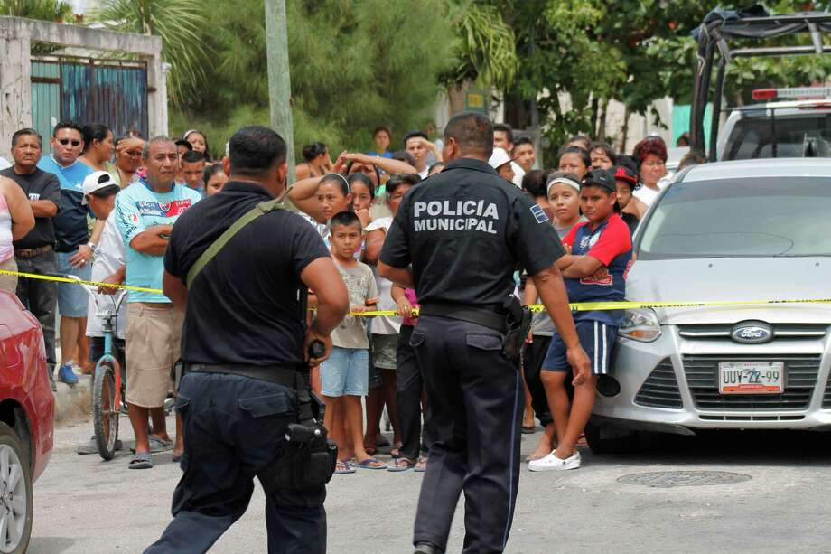 Onlookers stand behind a police line as municipal police secure the area after the bodies of five men and two women were found inside a home at a low income neighborhood in the resort city of Cancun, Mexico, Sunday April 14, 2013. The director of the Quintana Roo state detective agency says the victims' hands, heads and feet had been tied up with packing tape, and they apparently were asphyxiated. Photo: AP