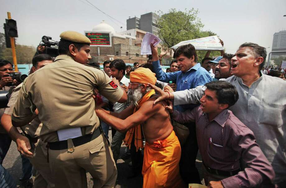 Indian protesters scuffle with a Delhi police officer outside the Police headquarters during a protest against the rape of a 5-year-old girl in New Delhi, India, Saturday, April 20, 2013. Officials say the child is in serious condition after being raped and tortured by a man who held her in a locked room in India's capital for two days. Police say the girl went missing Monday and was found Wednesday by neighbors who heard her crying in a room in the same New Delhi building where she lives with her parents. Photo: AP