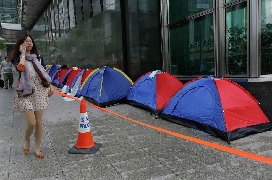A woman walks past tents set up by container workers during a protest outside Cheung Kong Center, which houses the headquarters of Hong Kong billionaire Li Ka-shing's company Hutchison Whampoa, in Hong Kong Friday, April 19, 2013. More than 200 striking dock workers camped out in action to force a concession over a pay dispute against Hong Kong International Terminals Ltd., a subsidiary of Hutchison Whampoa. Photo: AP