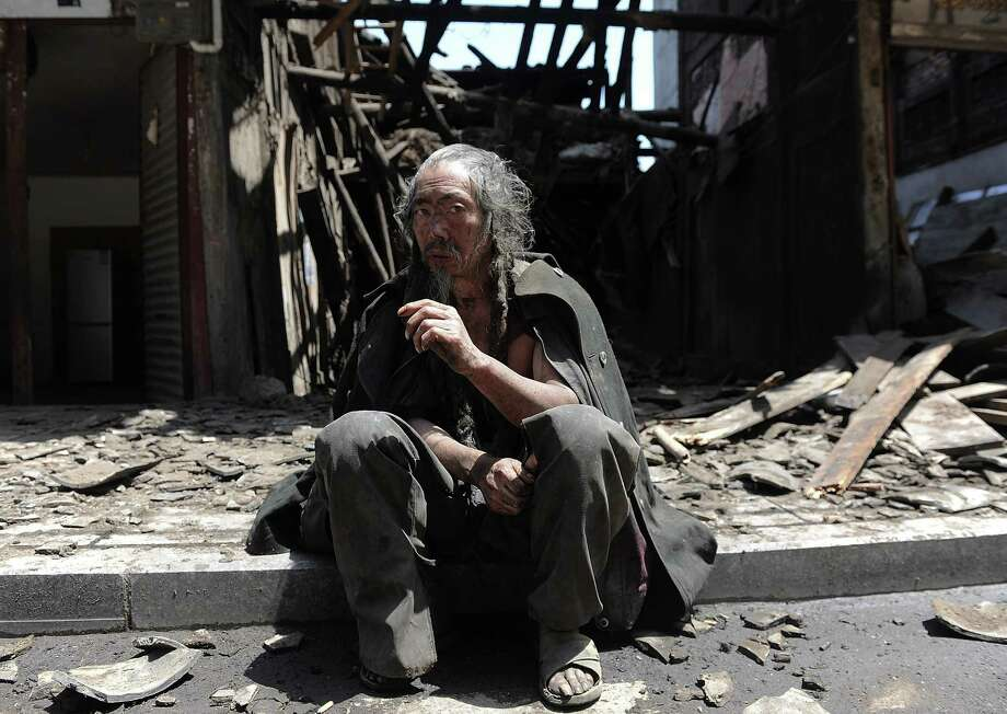 A man sits in front of the houses destroyed by an earthquake which hit Lushan county in Ya'an in southwest China's Sichuan province on Saturday, April 20, 2013. The powerful earthquake shook China's Sichuan province Saturday morning, nearly five years after a devastating quake jolted the province. (AP Photo) Photo: AP