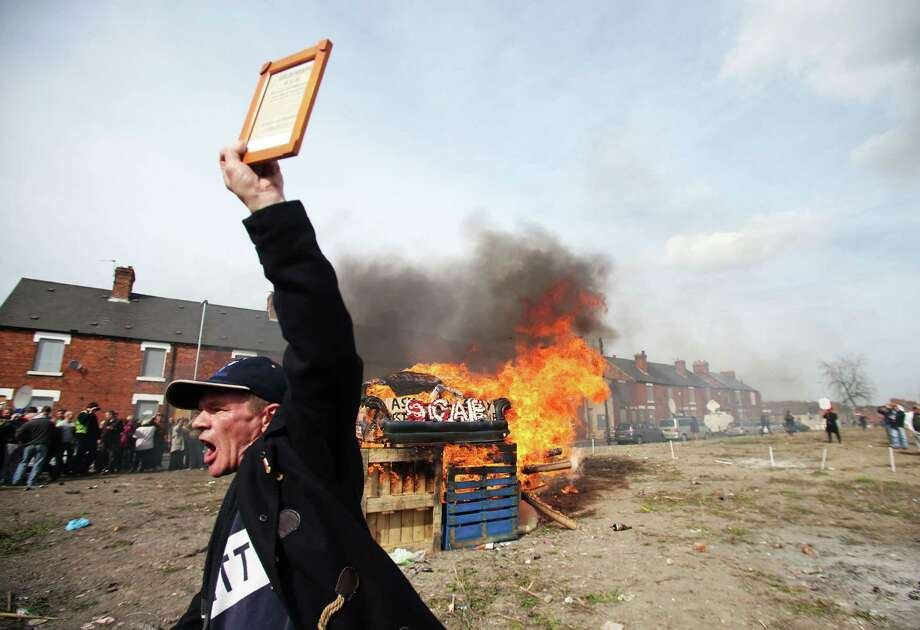 Protesters set fire to a coffin containing an effigy of Margaret Thatcher in Goldthorpe, northern England as people gather and march to celebrate her funeral in London Wednesday April 17, 2013. The death of Britain's first female Prime Minister has deeply split the nation between those who look back on her with respect and those who, like the coal miners with whom she had a bruising confrontation, deeply despised her. The divisive leader ruled the country for 11 years breaking the strength of the trade unions, securing victory in a distant war for the Falkland Islands, and selling off state-owned utilities at a record pace.(AP Photo / Lynne Cameron, PA) Photo: AP