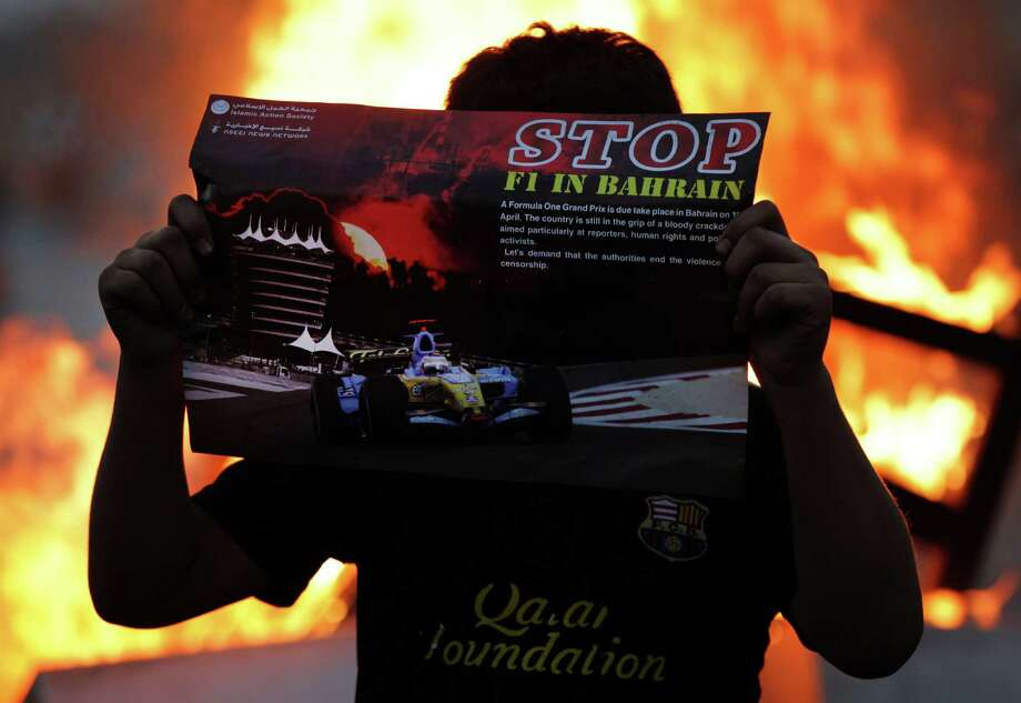 A Bahraini anti-government protester holds a poster opposing the upcoming Formula One Bahrain Grand Prix, to be held Sunday, next to a fire set by anti-government protesters during clashes with riot police firing tear gas in Qadam, Bahrain, on Friday, April 19, 2013. Clashes between protesters and police continued in Bahrain on Friday, ahead of Sunday's Formula One Grand Prix. Hardline protesters hope to embarrass the ruling royal family with increased violence, while more moderate protesters, who support the race, merely want to highlight their demands for a greater voice in the country. Photo: AP
