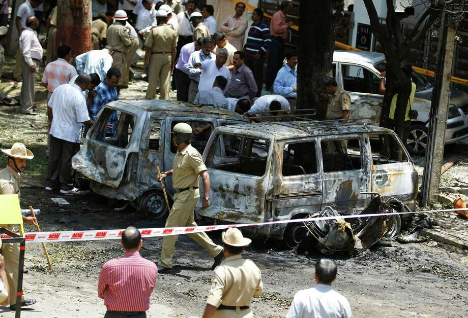 Policemen and officials inspect the site of an explosion at a residential neighborhood near the office of India's main opposition Bharatiya Janata Party in Bangalore, India, Wednesday, April 17, 2013. A powerful bomb exploded Wednesday near the office of the political party, injuring at least 16 people, police said. Photo: AP