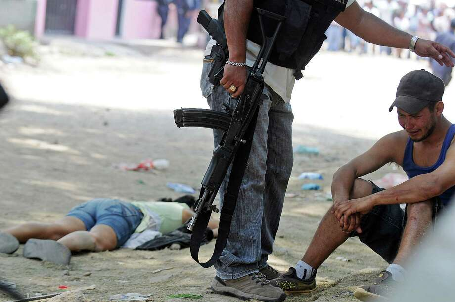 A policeman stands next to a man weeping next to the body of Maria Duron, a pregnant fruit vendor caught in the crossfire after gunmen opened fire on a vehicle, killing a sixteen year-old student, her police bodyguard and three other people who were on the street in the city of Tegucigalpa, Honduras, Monday April 15, 2013. According to the Honduras National Autonomous University's Observatory of Violence, Honduras has the highest homicide rate in the world. Photo: AP