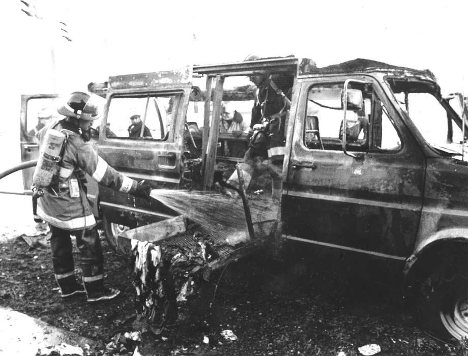 Firefighters extinguish the last burning pieces of a van that caught fire on April 26, 1988, trapping its handicapped driver inside. He was rescued by three men. Photo: File