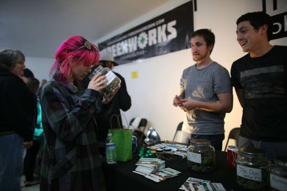 "A potential customer smells the product from Trees Collective during ""Studio 4/20,"" a legal marijuana celebration put on by DOPE Magazine at 7 Point Studios on April 20, 2013 on South Dearborn Street. The event billed itself as the largest local marijuana celebration since pot was legalized by Washington voters. (Joshua Trujillo, seattlepi.com) Photo: JOSHUA TRUJILLO, SEATTLEPI.COM"