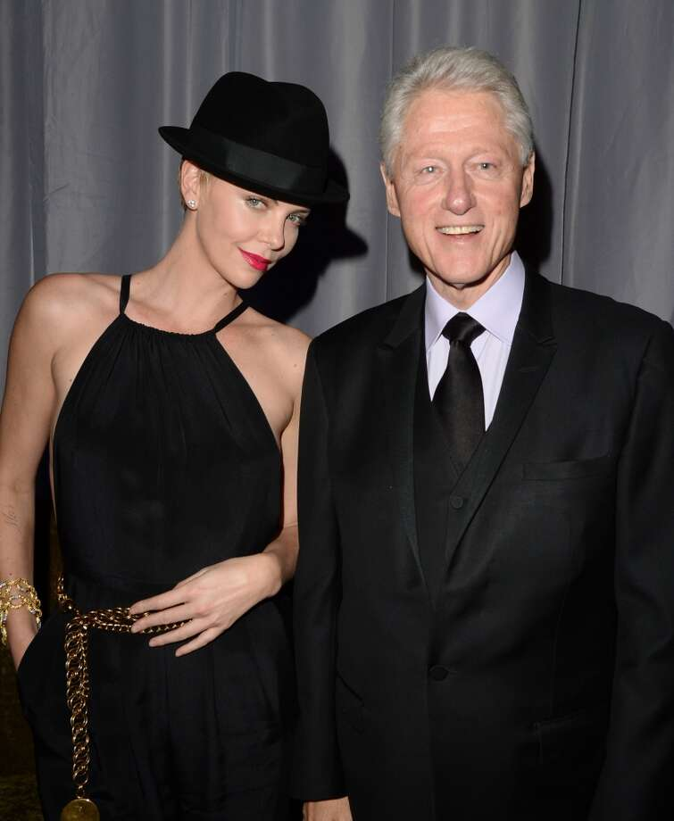 Former President of the United States Bill Clinton (R) gives actress Charlize Theron his hat backstage during the 24th Annual GLAAD Media Awards presented by Ketel One and Wells Fargo at JW Marriott Los Angeles at L.A. LIVE on April 20, 2013 in Los Angeles, California.  (Photo by Jason Merritt/Getty Images for GLAAD)