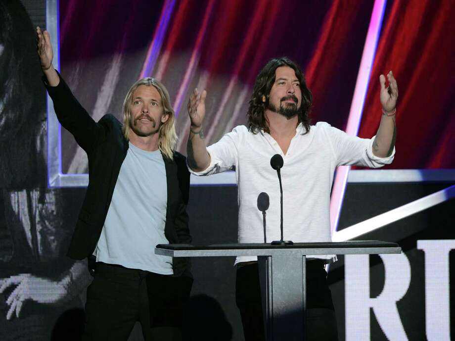 Musicians Taylor Hawkins (L) and Dave Grohl speak on stage at the 28th Annual Rock and Roll Hall of Fame Induction Ceremony at Nokia Theatre L.A. Live on April 18, 2013 in Los Angeles, California. Photo: Kevin Winter, Getty Images / 2013 Getty Images