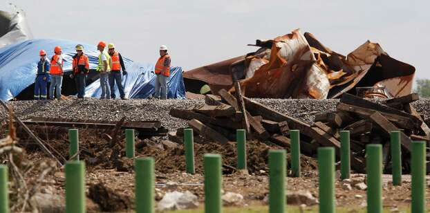 Workers stand among debris  Sunday, April 21, 2013, four days after an explosion at a fertilizer plant in West, Texas. The massive explosion at the West Fertilizer Co. Wednesday night killed 14 people and injured more than 160. (AP Photo/The Dallas Morning News, Michael Ainsworth, Pool) Photo: Michael Ainsworth, Associated Press / Pool The Dallas Morning News