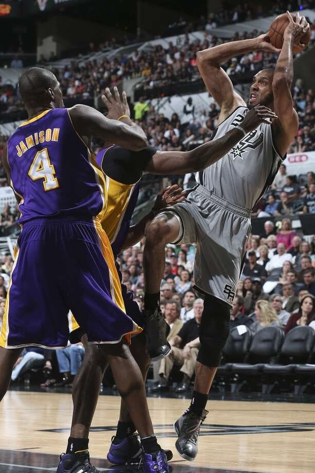 The Spurs\' Tim Duncan shoots out to the perimeter over Los Angeles Lakers\' Antawn Jamison (4), and Dwight Howard during the first half of Game 1 in the first round of the NBA Playoffs at the AT&T Center, Sunday, April 21, 2013.