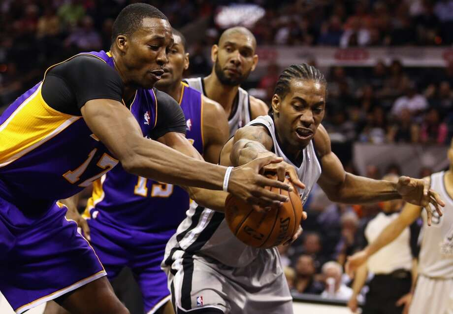 Kawhi Leonard (2) of the Spurs reaches for the ball against Dwight Howard (12) of the Los Angeles Lakers during Game 1 of the Western Conference Quarterfinals at AT&T Center on April 21, 2013.