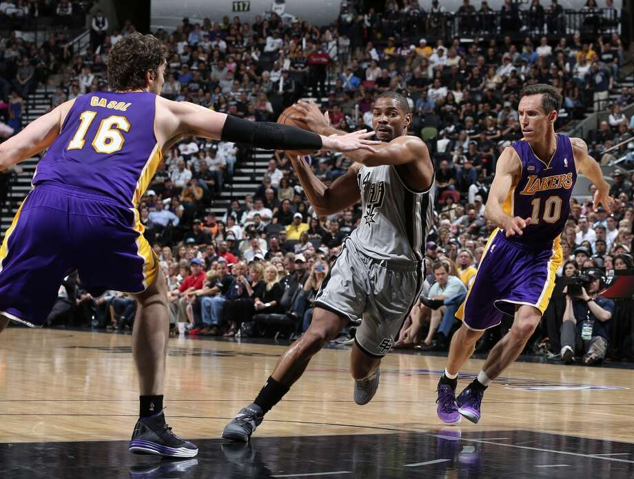 The Spurs\' Gary Neal drives through Los Angeles Lakers\' Pau Gasol and Steve Nash during the first half of Game 1 in the first round of the playoffs at the AT&T Center, Sunday, April 21, 2013.