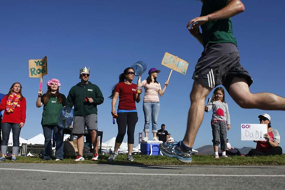 Employees of the Presidio Sports Basement cheer on runners as they make their way to the finish line during the Presidio 10k on Sunday, April 21 2013. The Presidio 10k supports the Guardsman Charity each year. Photo: James Tensuan, The Chronicle