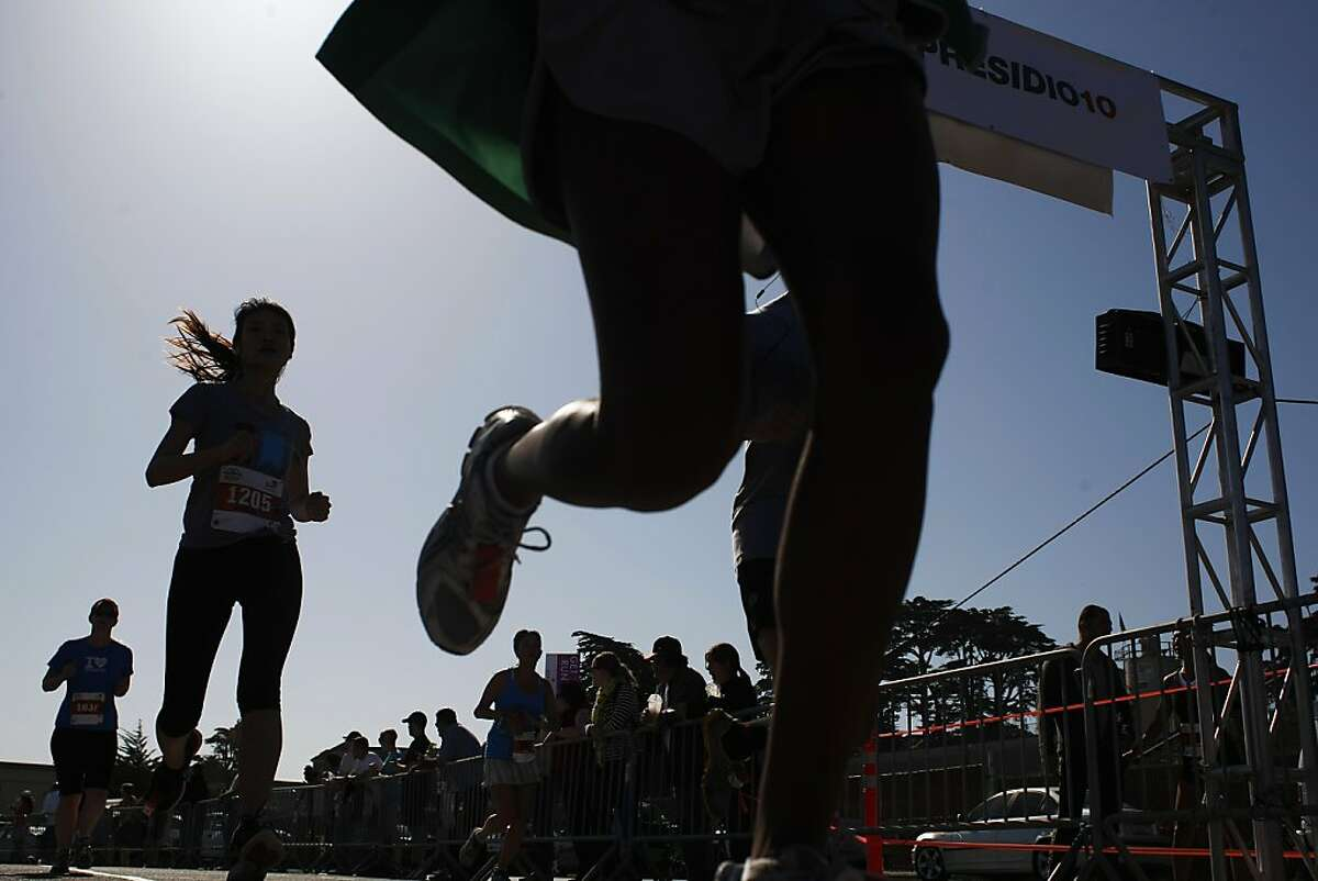 Participants cross the finish line after the Presidio 10 on Sunday, April 21 2013.