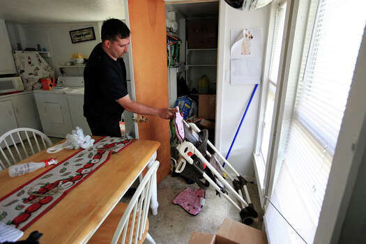 Robert Boles, 35, picks up a high chair, Sunday April 21, 2013, after an explosion at a fertilizer plant that occurred Wednesday evening in West, Tx. shattered windows in his home. Photo: Edward A. Ornelas, San Antonio Express-News / © 2013 San Antonio Express-News