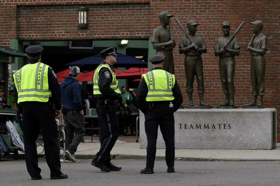 Police officers stand near statues of former Boston Red Sox greats, from left, Ted Williams, Bobby Doerr, Johnny Pesky and Dom DiMaggio during a baseball game between the Kansas City Royals and the Boston Red Sox, the first game held in the city following the Boston Marathon explosions, Saturday, April 20, 2013, in Boston.  Police captured Dzhokhar Tsarnaev, 19, the surviving Boston Marathon bombing suspect, late Friday, after a wild car chase and gun battle earlier in the day left his older brother dead. Photo: Julio Cortez