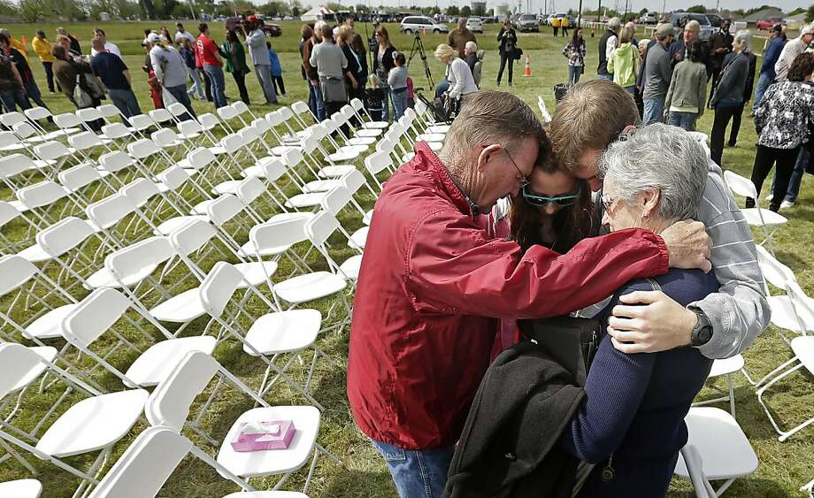 Churchgoers huddle to pray after a service for the First Baptist Church in a field Sunday, April 21, 2013, four days after an explosion at a fertilizer plant in West, Texas. The church could not meet in their building because it was in a damage zone after a massive explosion at the West Fertilizer Co. Wednesday night that killed 14 people and injured more than 160. (AP Photo/Charlie Riedel) Photo: Charlie Riedel, Associated Press
