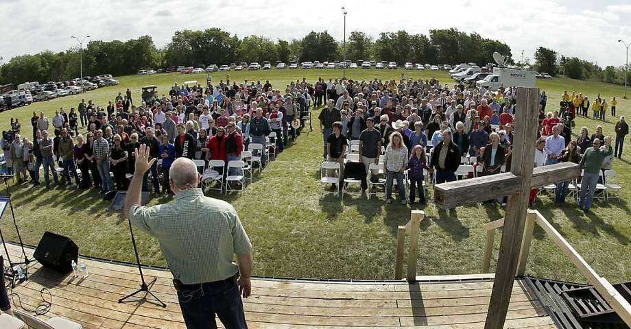 Pastor John Crowder delivers a sermon for the First Baptist Church from an 18-wheeler parked in a hay field. Photo: Charlie Riedel, Associated Press