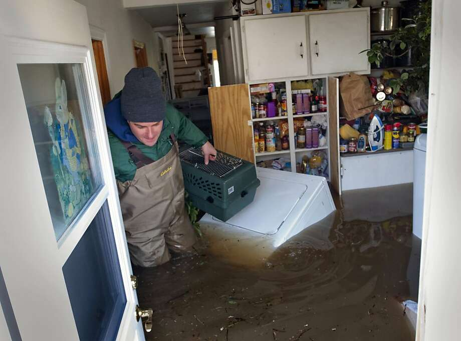 Joe Biggerstaff wades past a floating clothes dryer in his mother's Konkle Drive home on the Grand River north of downtown Grand Rapids, Mich., Sunday, April 21, 2013. The rising Grand River has driven hundreds of people from their homes in several western Michigan communities and was pushing Sunday toward a record high near Grand Rapids. (AP Photo/MLive.com, Chris Clark) Photo: Chris Clark, Associated Press