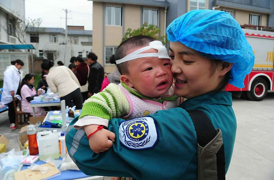 A Chinese medical worker holds an injured child in Longmen township, a town close to the epicentre of the earthquake that hit the city in Ya'an, southwest China's Sichuan province on April 21, 2013. Thousands of rescue workers combed through flattened villages in southwest China on Sunday in a race to find survivors from a powerful quake as the toll of dead and missing rose past 200. CHINA OUT   AFP PHOTOSTR/AFP/Getty Images Photo: Str, AFP/Getty Images