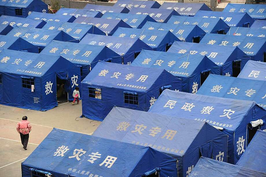 Residents walk among tents in the temporary settlement in Longmen township, a town close to the epicentre of the earthquake that hit the city in Ya'an, southwest China's Sichuan province on April 21, 2013. Thousands of rescue workers combed through flattened villages in southwest China on Sunday in a race to find survivors from a powerful quake as the toll of dead and missing rose past 200. CHINA OUT   AFP PHOTOSTR/AFP/Getty Images Photo: Str, AFP/Getty Images