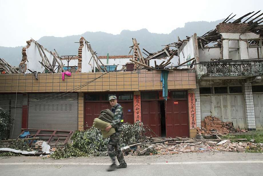 A soldier carries blankets in Gaohe, China, where many residents lost their homes in a quake that killed at least 188 people and hurt more than 11,000. Many in hard-hit villages said relief was slow to arrive. Photo: Sim Chi Yin, New York Times