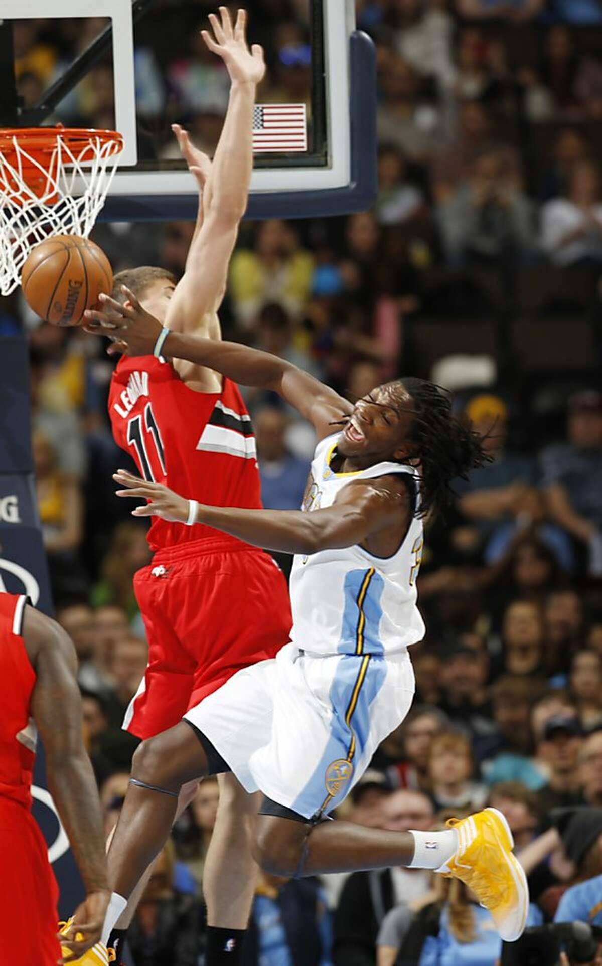 Denver Nuggets forward Kenneth Faried, front, collides with Portland Trail Blazers center Meyers Leonard while driving the lane in the first quarter of an NBA basketball game in Denver on Sunday, April 14, 2013. Inital reports from the team say that Faried suffered a sprained ankle on the play and was forced to leave the game. (AP Photo/David Zalubowski)
