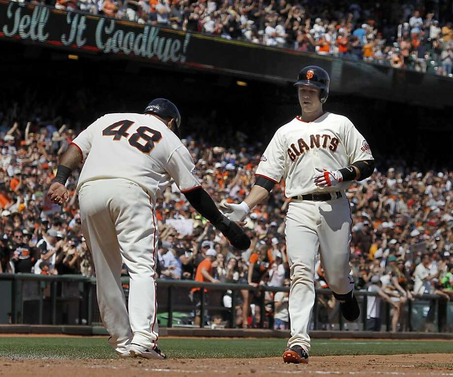 Buster Posey gets a low-five greeting from Pablo Sandoval and a feeling of relief after hitting his first home run of the season. Photo: Brant Ward, The Chronicle