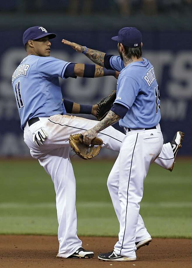 Tampa Bay Rays shortstop Yunel Escobar, left, and third baseman Ryan Roberts celebrate after the team defeated the Oakland Athletics 8-1 during an MLB American League baseball game Sunday, April 21, 2013, in St. Petersburg, Fla. (AP Photo/Chris O'Meara) Photo: Chris O'Meara, Associated Press