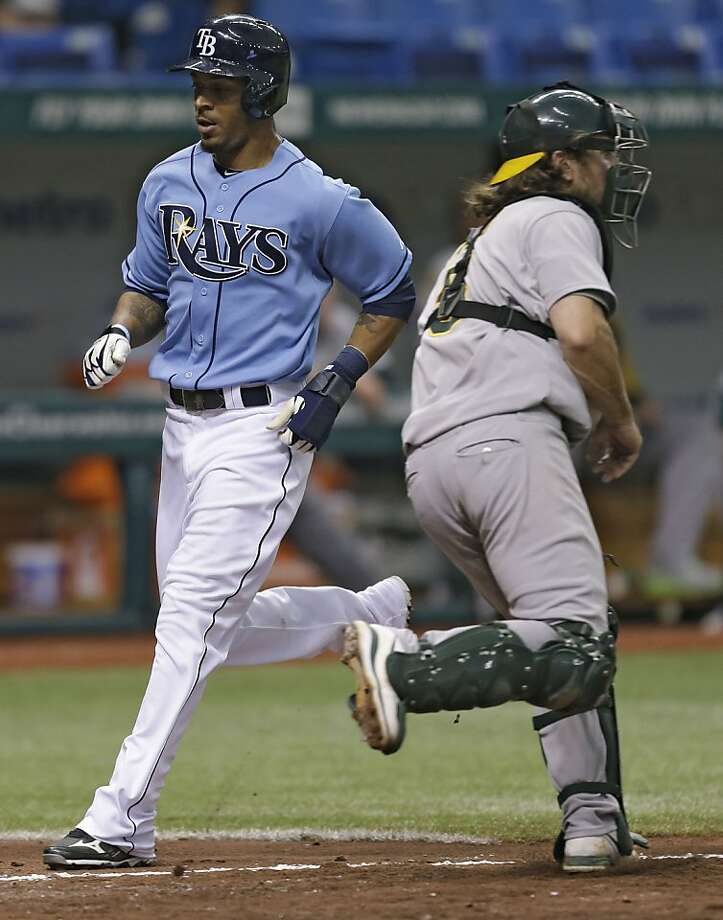 Tampa Bay Rays' Desmond Jennings, left, scores past Oakland Athletics catcher John Jaso during the seventh inning of a baseball game Sunday, April 21, 2013, in St. Petersburg, Fla. Jennings scored on an RBI double by Ryan Roberts. (AP Photo/Chris O'Meara) Photo: Chris O'Meara, Associated Press