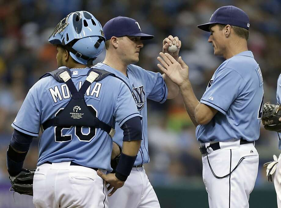 Tampa Bay Rays pitching coach Jim Hickey, right, talks to relief pitcher Jake McGee, center, as catcher Jose Molina looks on during the seventh inning against the Oakland Athletics during a baseball game Sunday, April 21, 2013, in St. Petersburg, Fla. (AP Photo/Chris O'Meara) Photo: Chris O'Meara, Associated Press