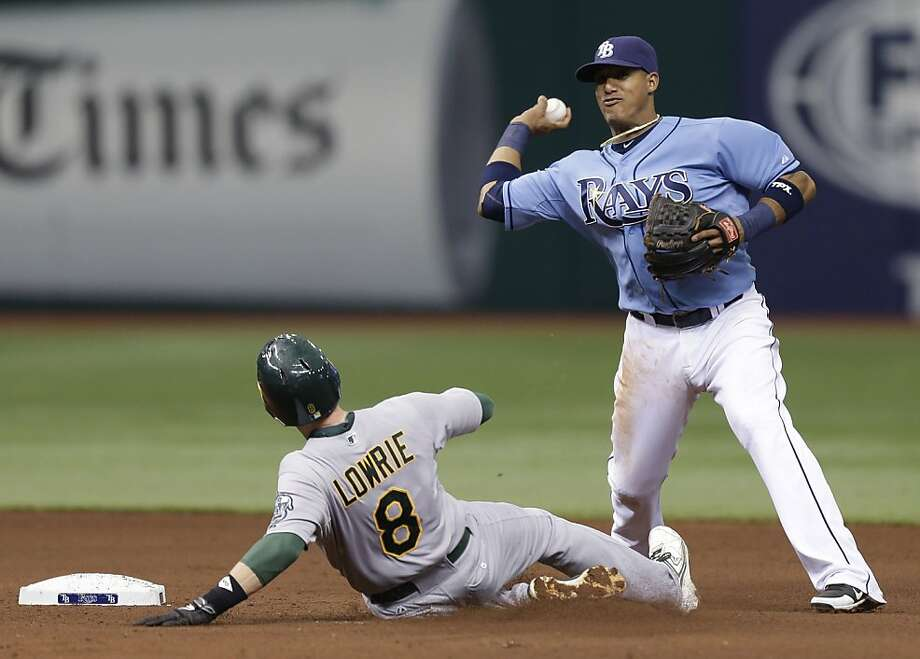 Tampa Bay Rays shortstop Yunel Escobar, right, forces out Oakland Athletics' Jed Lowrie at second base on a fourth-inning fielder's choice during a baseball game on Sunday, April 21, 2013, in St. Petersburg, Fla. Oakland's Brandon Moss was safe at first base. (AP Photo/Chris O'Meara) Photo: Chris O'Meara, Associated Press
