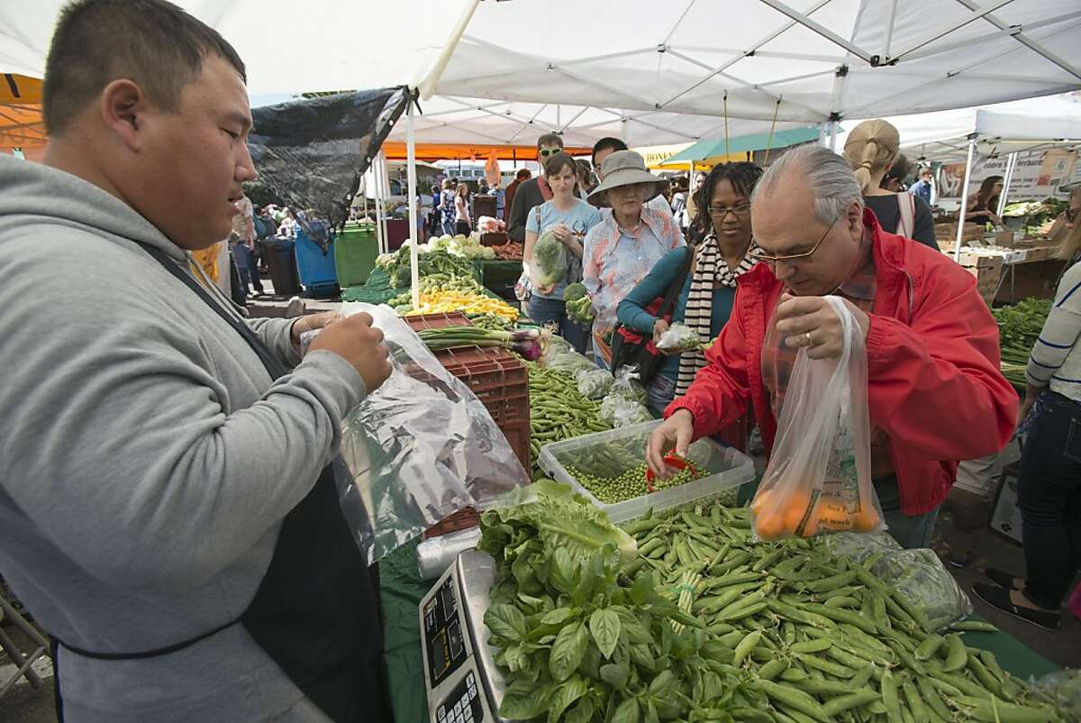 John Mendelson, right loads up some English Peas as produce owner Kou Her, left, looks on at the Noe Valley Farmers Market in San Francisco, Calif. on April 20, 2013.