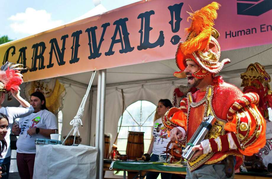 Glen Johnson, of Houston, tries on a Carnival costume during the 43rd Annual Houston International Festival, Sunday, April 21, 2013, in Houston. The festival ail continue through April 27-28th, 11 a.m. to eight p.m. The festival features seven stages, a Brazilian living museum and six multicultural markets. Photo: Nick De La Torre, Chronicle / © 2013 Houston Chronicle