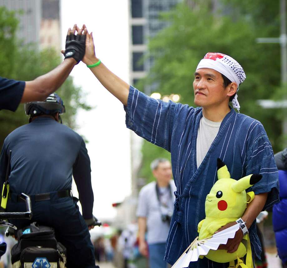 Mark Takayama, of the Japan American Society gives a Houston Police officer a high five as he attracts pedestrians to his society's booth during the 43rd Annual Houston International Festival, Sunday, April 21, 2013, in Houston. The festival ail continue through April 27-28th, 11 a.m. to eight p.m. The festival features seven stages, a Brazilian living museum and six multicultural markets. Photo: Nick De La Torre, Chronicle / © 2013 Houston Chronicle