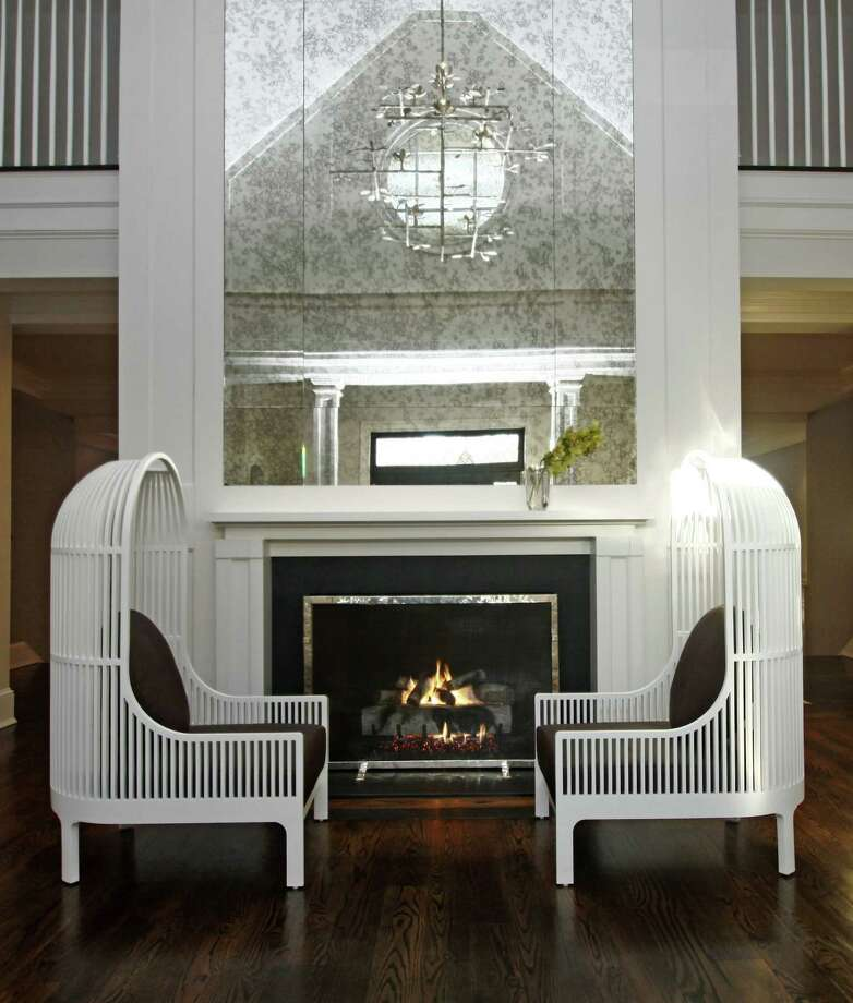 "Several pieces of furniture could as easily be classified as art in this ""Seaside Sophistication"" home in Westport, notably the silver painted rope console table and two rope chairs (Centour and Centori) by Christian Astuguevielle for Holly Hunt. The tree stump tables were found in New York City's SoHo area. Photo: Contributed Photo"