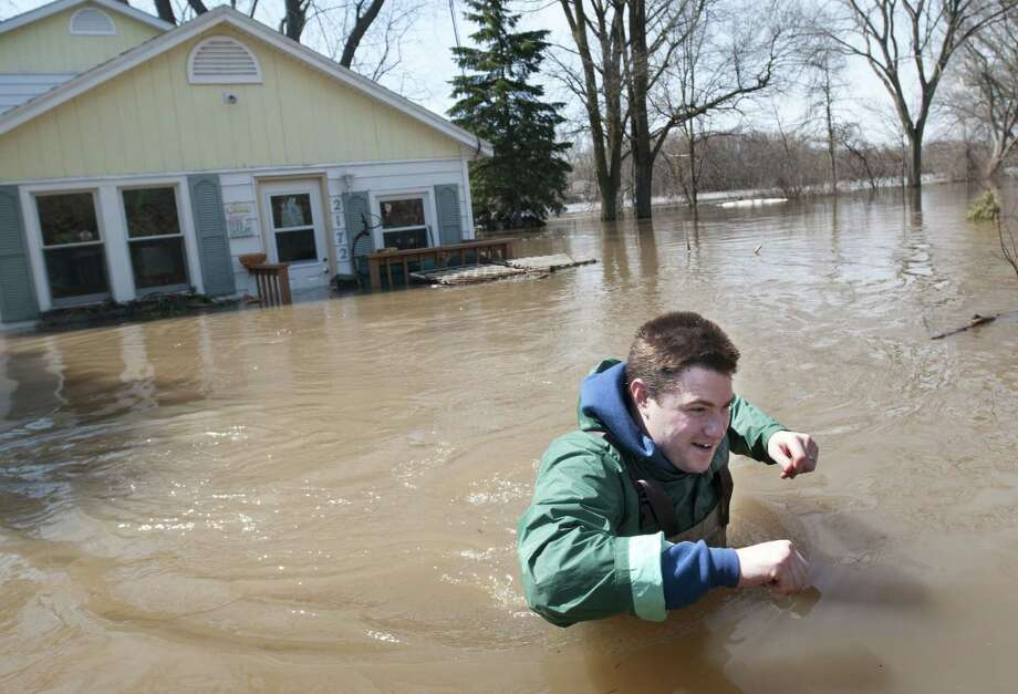 Joe Biggerstaff wades away from his mother's home on the Grand River north of downtown Grand Rapids, Mich., on Sunday. Waters have driven hundreds from their homes in several western Michigan communities. Photo: Chris Clark, MBI / MLive.com