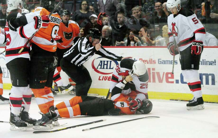 Albany Devils? Mike Hoeffel, center, is removed from the top of Garret Roe of the Adirondack Phantoms, Sunday evening April 21, 2013, after the pair spared in a second period tangle at the Times Union Center. (Will Waldron/Times Union) Photo: Will Waldron