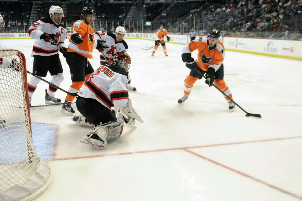 Albany Devils? goalie Scott Wedgewood, left, gets ready make a save off Jon Sim, right, in the third period against the Adirondack Phantoms, Sunday evening April 21, 2013, at the Times Union Center in Albany, N.Y. (Will Waldron/Times Union)