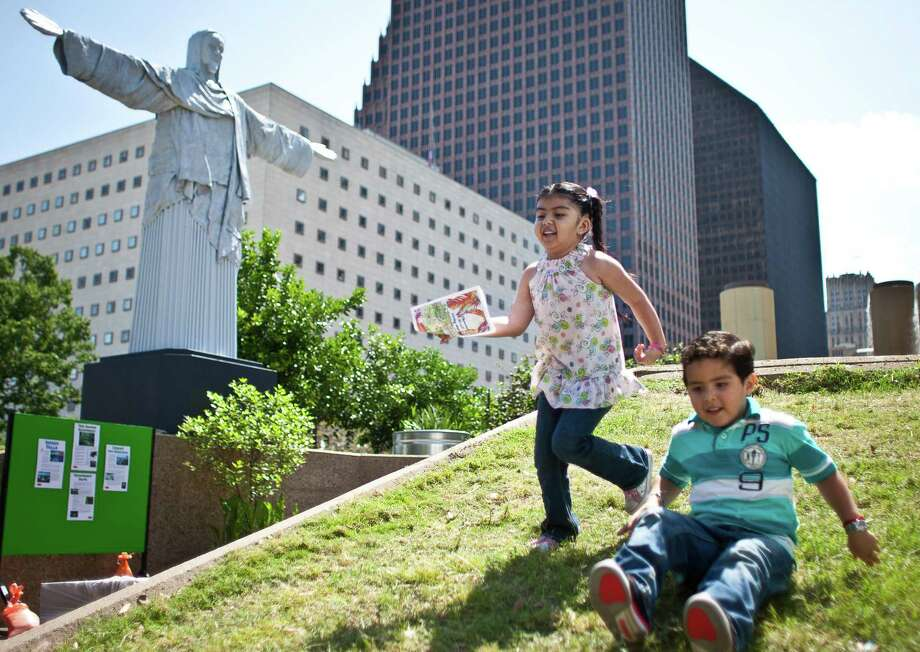 Natalia Cruz, 4, and her cousin Alexander Sandoval, 5, play on a hill by the Brazil Living Museum section of the 43rd annual Houston International Festival, Sunday in Houston. The festival continues next weekend. Photo: Nick De La Torre, Staff / © 2013 Houston Chronicle