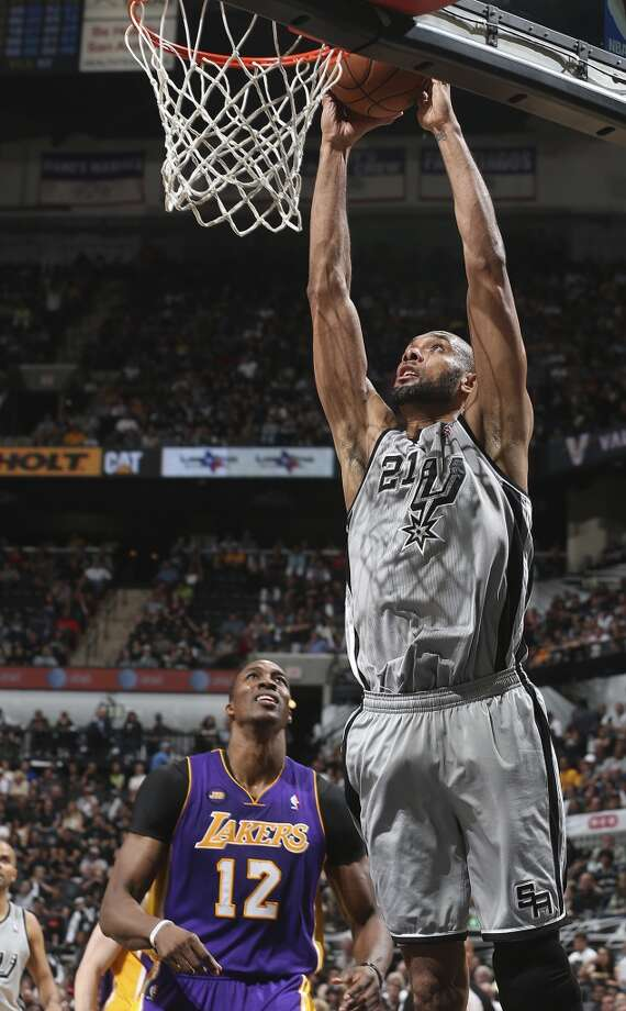 San Antonio Spurs\' Tim Duncan dunks over Los Angeles Lakers\' Dwight Howard during the first half of game 1 in the first round of the NBA Playoffs at the AT&T Center, Sunday, April 21, 2013.