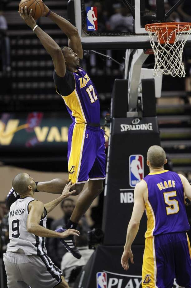 Los Angeles Lakers\' Dwight Howard dunks an alley-oop over San Antonio Spurs\' Tony Parker during the first half of game 1 in the first round of the NBA Playoffs at the AT&T Center, Sunday, April 21, 2013.