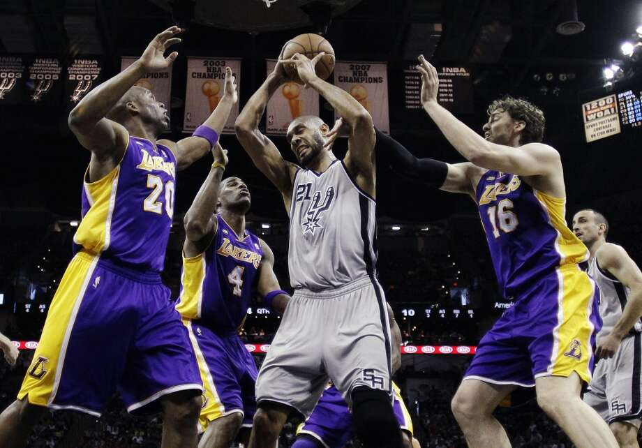 San Antonio Spurs\' Tim Duncan (21) grabs a rebound between Los Angeles Lakers\' Jodie Meeks (20), Antawn Jamison (4) and Pau Gasol (16) during the first half of Game 1 of their first-round NBA playoff basketball series, Sunday, April 21, 2013, in San Antonio.