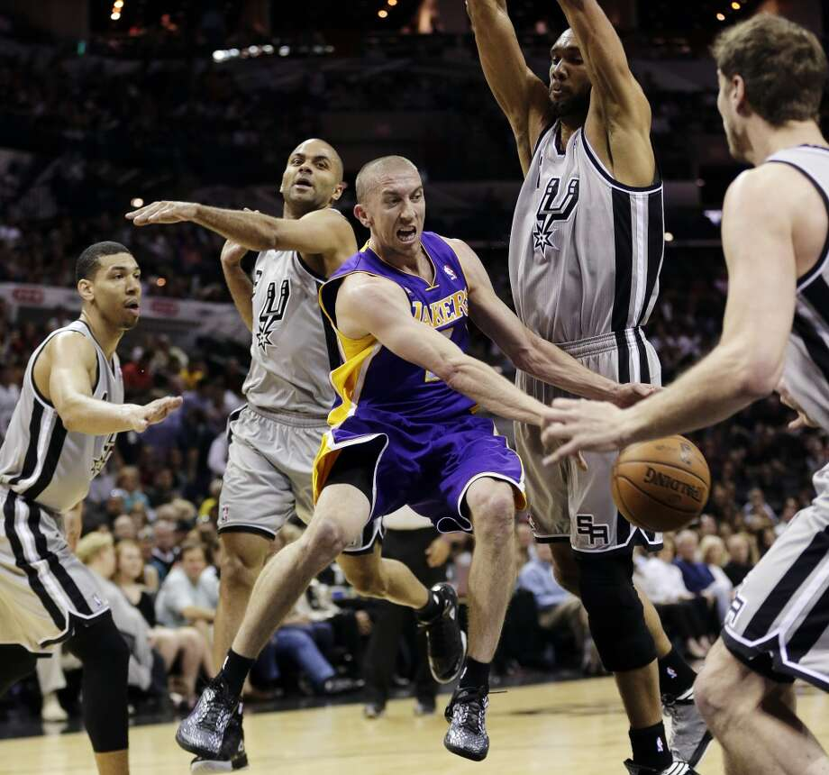 Los Angeles Lakers\' Steve Blake, center, is surrounded by San Antonio Spurs\', from left, Danny Green, Tony Parker, Tim Duncan and Tiago Splitter as he tries to drive to the basket during the first half of Game 1 of their first-round NBA playoff basketball series, Sunday, April 21, 2013, in San Antonio.