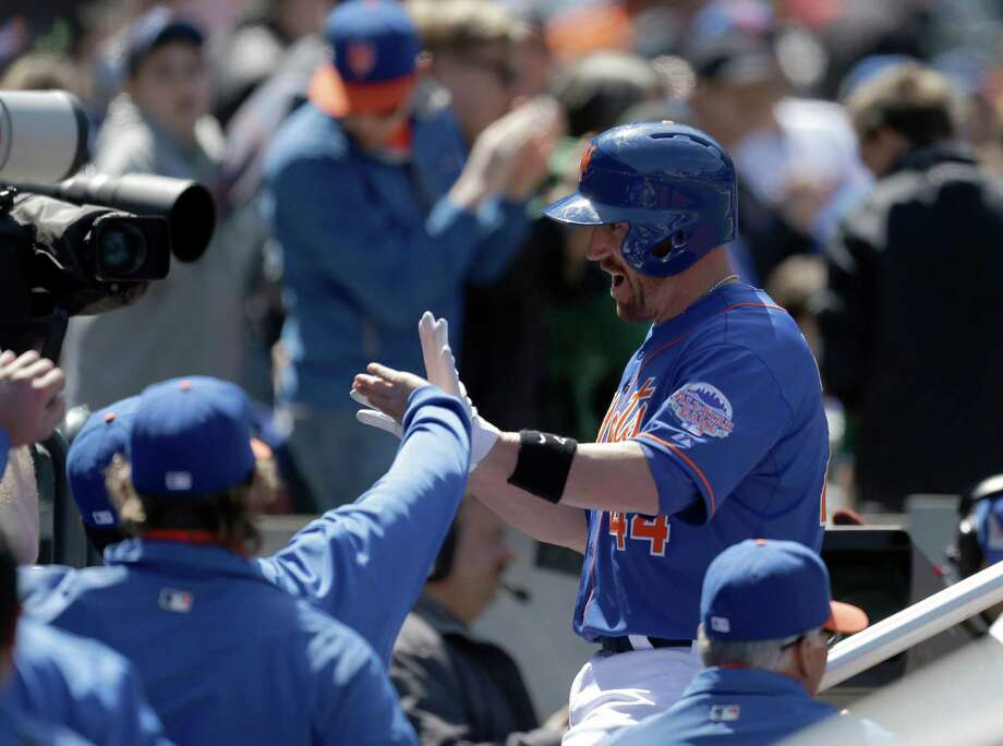 New York Mets John Buck is greeted at the dugout after hitting a second-inning solo home run off Washington Nationals starting pitcher Jordan Zimmermann (27) in an MLB National League baseball game at Citi Field in New York Sunday, April 21, 2013. (AP Photo/Kathy Willens) Photo: Kathy Willens