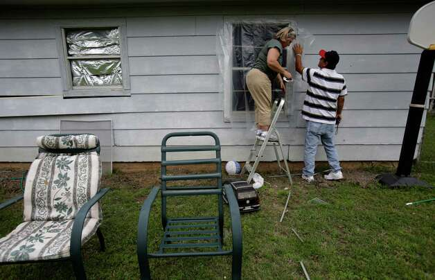 Pete Arias, right, holds plastic in place over a blown out window as his wife Jacki staples it in place. Families were let back in to see their homes which were damaged by the explosion in West, TX on Sunday April 21, 2013. Photo: Bob Owen, Express-News / ©2013 San Antonio Express-News